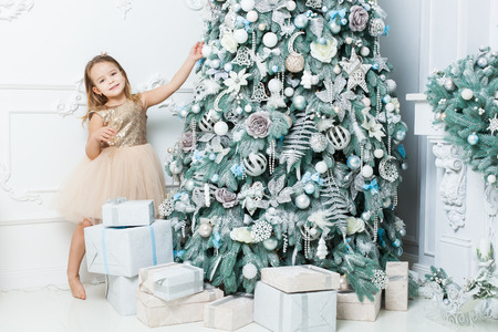 Cute girl in a beautiful dress decorates the Christmas tree with toys.