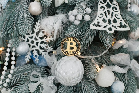 Gold coin of bitcoin lying on a white ball among the toys of the Christmas tree. Imagens