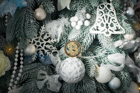 Gold coin of bitcoin lying among the toys of the Christmas tree. Banque d'images - 117954560