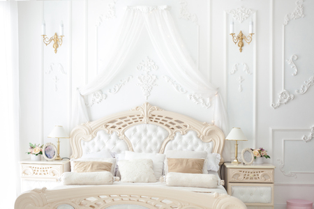 Beautiful big bed in the bedroom in rococo style.