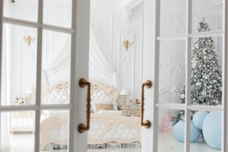 The door to the bedroom is ajar. In the bedroom is a Christmas tree.