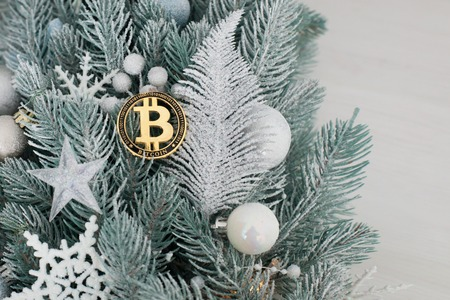 Bitcoin among the Christmas toys on the branches of the Christmas tree. Banque d'images - 117954612