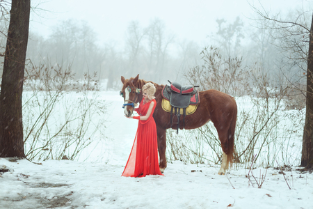 Woman in a red dress in the winter forest. She strokes a horse.