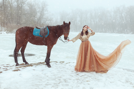 Beautiful young woman in an elegant dress standing by a frozen lake. She holds a horse for the reins. Imagens