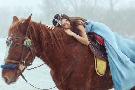 Beautiful young woman riding a horse. Its snowing.