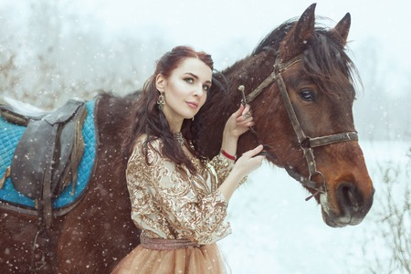 Beautiful young woman stands near the horse. They are in a winter park. Banque d'images - 117955138