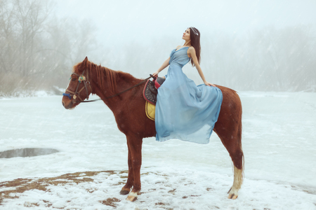 Young beautiful brunette riding a horse by a frozen lake. Banque d'images - 117955181