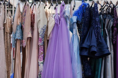 Beautiful shiny evening gowns hang on a hanger. Imagens
