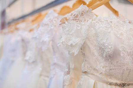 Beautiful wedding dresses hang on hangers in the bridal salon. Banque d'images - 117955207