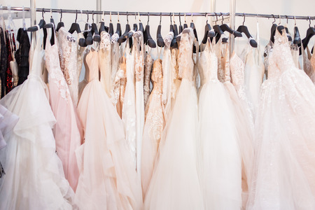 Stand with many beautiful wedding dresses in the showroom.