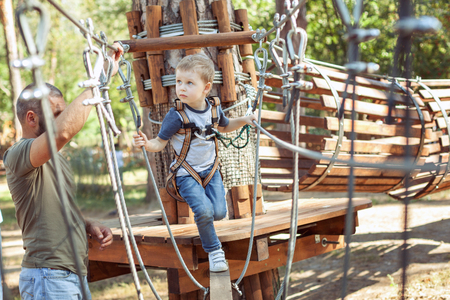 Young father helps his son overcome obstacles in extreme park.