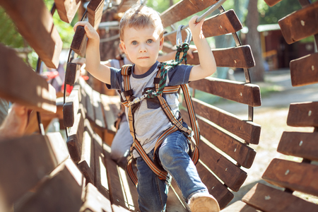 Little boy overcomes an obstacle in an extreme park. Imagens