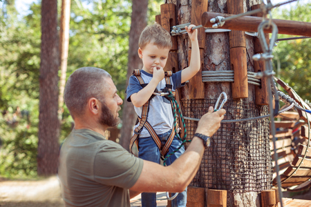 Dad helps his son overcome obstacles in extreme park. Imagens