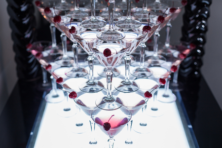 Pyramid of martini glasses with cherries on a party.