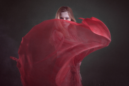 Beautiful young woman in a red dress in a dark room among the flour. Banque d'images - 117956231