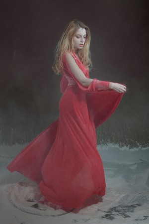 Beautiful young woman in red dress dancing in flour. Banque d'images - 117956232