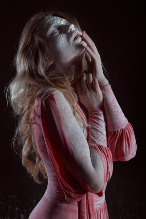 Portrait of a beautiful woman in a red dress in the dark. She is covered with white powder.