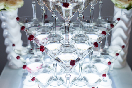 Pyramid of martini glasses with cherries on a holiday. Banque d'images - 121821255