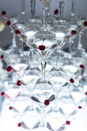 Pyramid of martini glasses with cherries on a holiday. Imagens