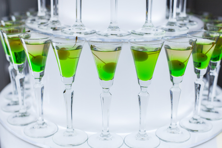 Glasses with a green cocktail and olive stand on the table at a party.