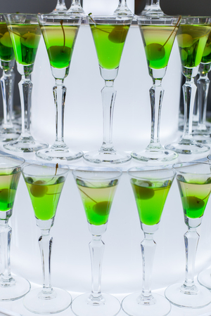 Glasses with a green cocktail and olive stand on the table at a party. Banque d'images - 121838429