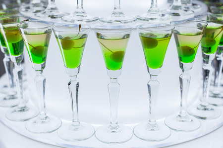 Glasses with a green cocktail and olive stand on the table at a party. Banque d'images - 121838432
