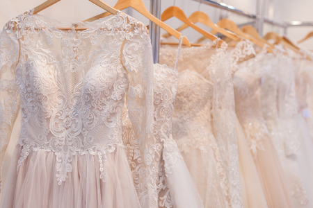 Beautiful lace wedding dresses on hangers in the showroom. Imagens