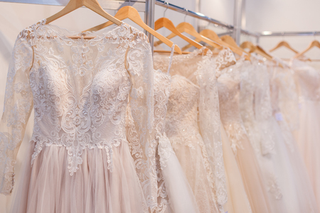 Beautiful lace wedding dresses on hangers in the showroom. Banque d'images - 121838437