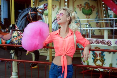Young blonde woman standing near a carousel and holding a cotton candy.