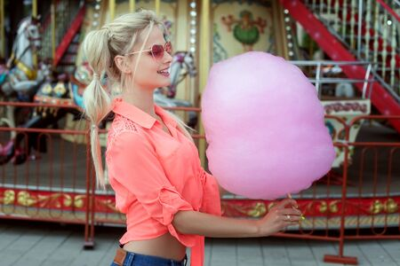 Young blond woman holding pink cotton candy in her hands.
