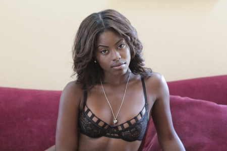 Beautiful young African-American girl in black lace bra lingerie and necklace smiling on velvet couch photo