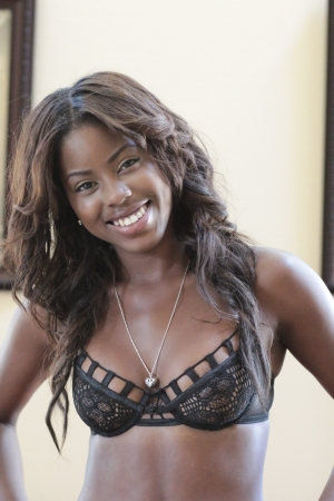 Beautiful African-American girl posing in black lace lingerie bra with necklace smiling  photo