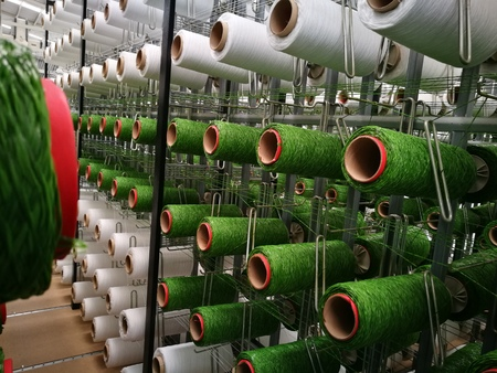 White and green yarns in racks for artificial grass weaving machines.