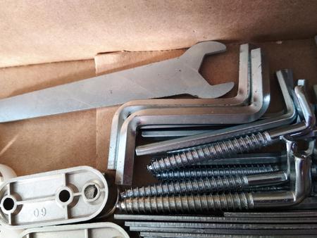 Ironmongery silver bronze iron stainless steel wrench tapping screw repair cardboard background macro photo.