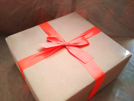 Craft cardboard paper box orange ribbon bow gift surprise present photo.
