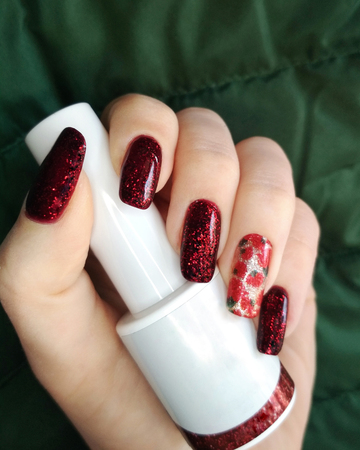 Woman hand finger black and red flower manicure gel nail polish swatch design white bottle beauty fashion photo.