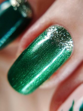 Woman hand finger green silver glitter shimmer manicure gel nail polish swatch design beauty fashion macro photo. Stok Fotoğraf
