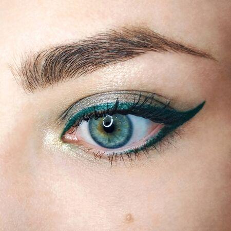 Blue eye gold green arrow eyeliner make-up eyebrow lash cosmetic swatch fashion macro photo.