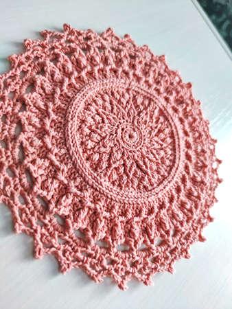 Knitting crochet doily napkin cotton pink yarn thread hook craft creative closeup macro photo. Stock fotó