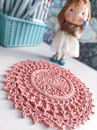 Knitting crochet doily napkin cotton pink yarn thread hook craft creative fairy doll statue basket closeup macro photo.
