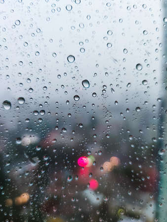 Rain raindrops on the window glass evening city lights macro photo. Stock fotó