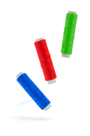 alteration shop: Three linen thread roles green Red blue before white background
