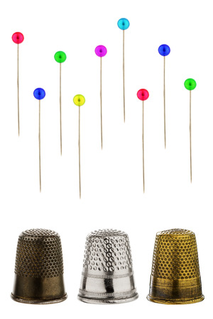 alteration shop: Three thimbles with pins before white background Stock Photo