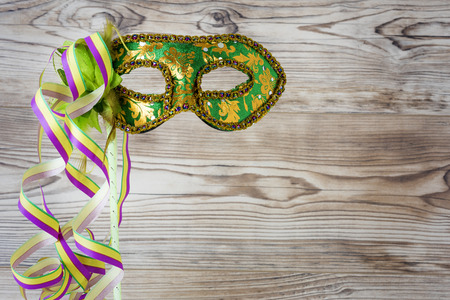 fasching: Green carnival mask before a wooden wall