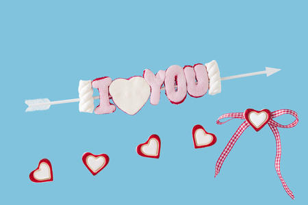 I love you arrow and hearts before blue background