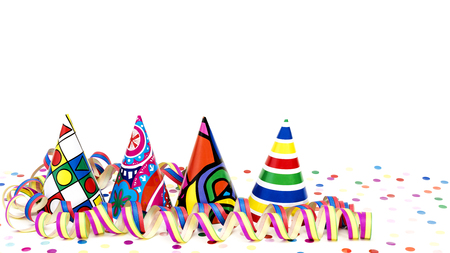 Coloured party hats and streamers before white background Stock Photo