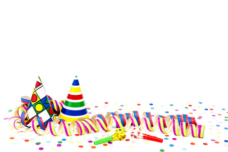 Streamers and party hats before white background