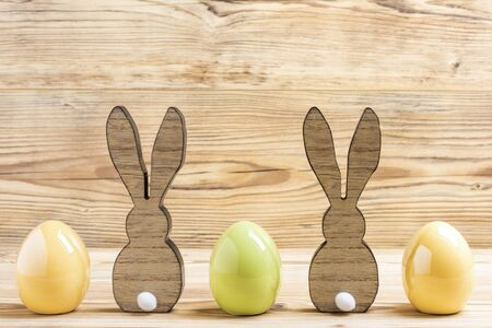 Two easter bunnies with three easter eggs in front of a wood background Фото со стока