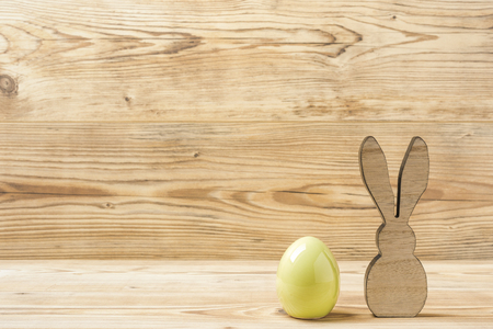 An easter egg and an easter bunny in front of a wood background Фото со стока