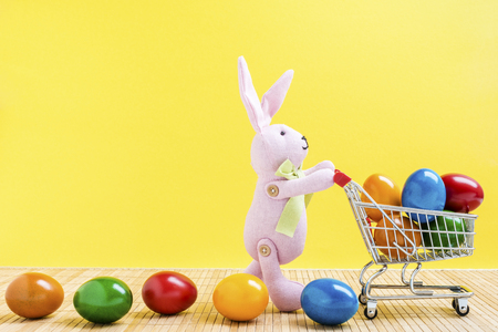 Easter bunny with shopping cart and colorful easter eggs in front of a yellow background